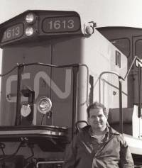 Charles Bohi stands in front of a parked train car.