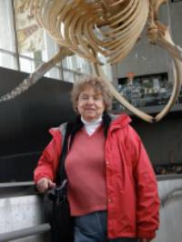 Susan Brown poses in a museum near a dinosaur skeleton.